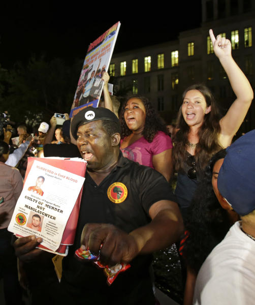 FILE - In this Saturday, July 13, 2013 file photo, James Evan Muhammad, front left, of the New Black Panther Party, shouts slogans after the verdict of not guilty was handed down in the trial of George Zimmerman at the Seminole County Courthouse, in Sanford, Fla. Neighborhood watch captain George Zimmerman was cleared of all charges Saturday in the shooting of unarmed teenager Trayvon Martin. Nearly 70 years after Jackie Robinson was run out of town by the KKK, Sanford is absorbing what some see as another blow to race relations: Zimmerman's acquittal. (AP Photo/John Raoux, File)