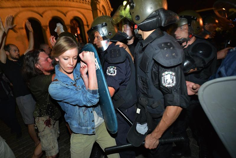 Protesters clash with Bulgarian riot police during an anti-government protest in front of the parliament building in Sofia Tuesday, July 23, 2013. Police in riot gear pushed away the protesters and formed a corridor to allow those trapped since Tuesday out of the building. Anti-government protests in Bulgaria's capital have been going on for 40 days, and escalated on Tuesday evening as several hundred demonstrators trapped 109 people — including three ministers, some 30 lawmakers and their staff — inside Parliament. (AP Photo/Georgi Kozhuharov)