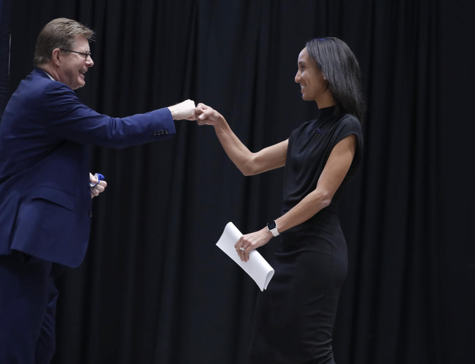 Nina King fist-bumps Duke President Vincent Price during a press conference where she was introduced as Duke's new athletic director, Friday, May 21, 2021, at Cameron Indoor Stadium in Durham, N.C. (Ethan Hyman/The News & Observer via AP)