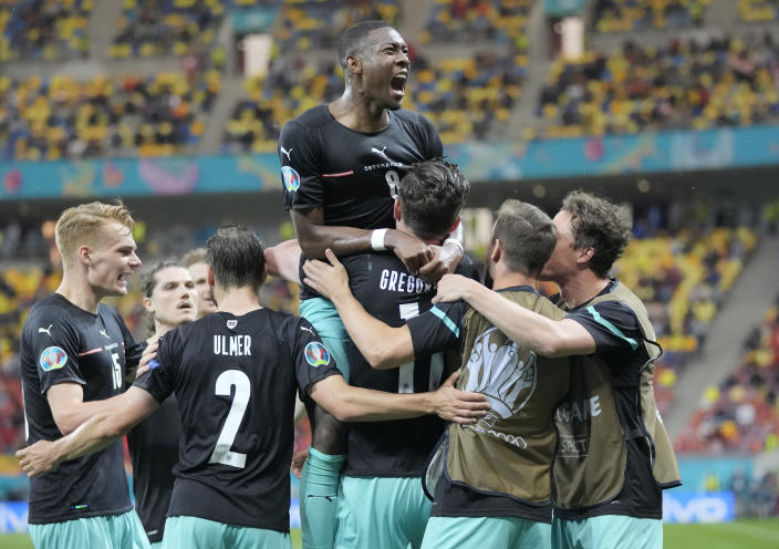 Austria's Michael Gregoritsch, center down, celebrates with teammates after scoring his side's second goal during the Euro 2020 soccer championship group C match between Austria and Northern Macedonia at the National Arena stadium in Bucharest, Romania, Sunday, June 13, 2021. (AP Photo/Vadim Ghirda, Pool)