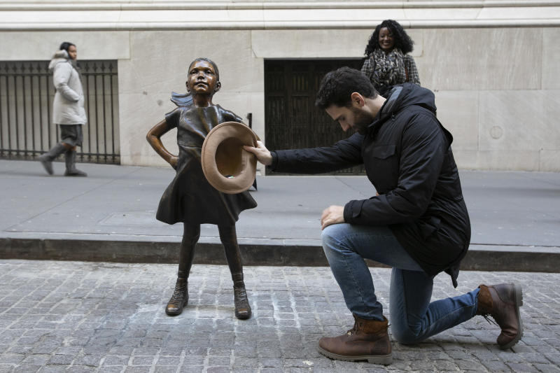 "Angel Luis Rodriguez Santisteban kneels before the ""Fearless Girl"" statue after it was unveiled at its new location in front of the New York Stock Exchange, Monday, Dec. 10, 2018, in New York. The tourist from Barcelona said, ""I tip my hat because I admire her."" (AP Photo/Mark Lennihan)"