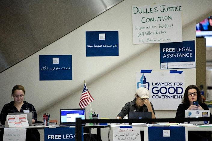 Volunteers wait to offer free legal advice to travelers at the international arrivals hall at Washington Dulles International Airport on February 6, 2017 (AFP Photo/Brendan Smialowski)