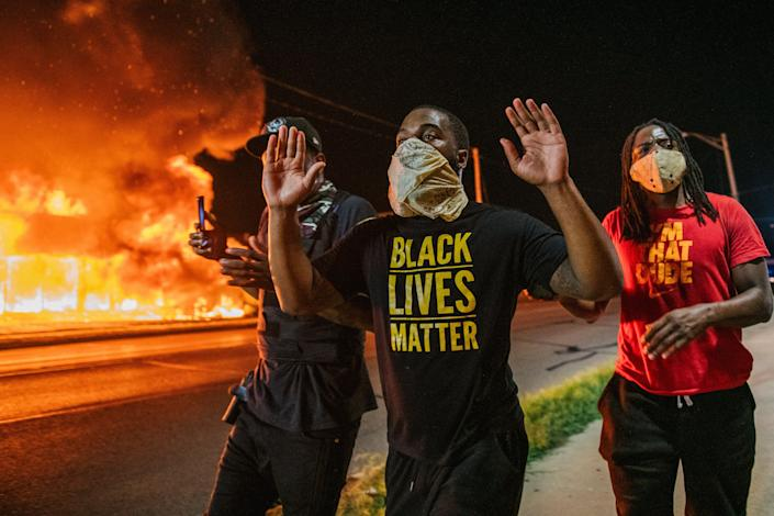<p>Men walk towards law enforcement with their hands up on August 24, 2020 in Kenosha, Wisconsin. A second night of civil unrest occurred after the shooting of Jacob Blake, 29, on August 23.</p> (Photo by Brandon Bell/Getty Images)