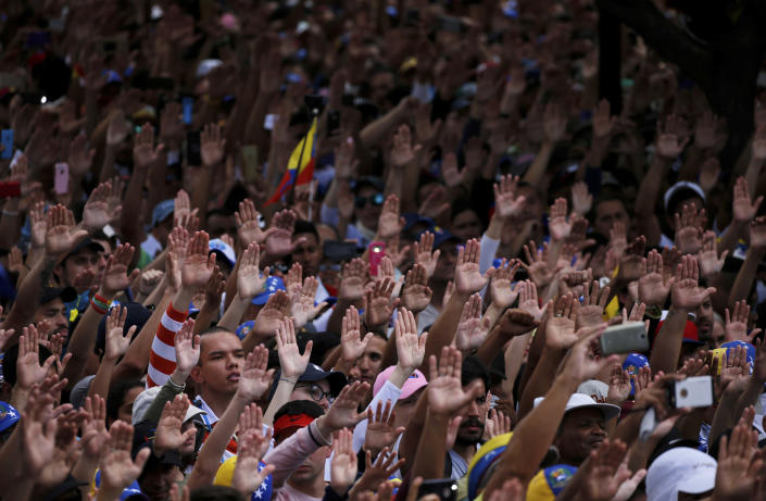 Anti-government protesters hold their hands up during the symbolic swearing-in of Juan Guaido, head of the opposition-run congress who declared himself interim president of Venezuela during a rally demanding President Nicolas Maduro's resignation in Caracas, Venezuela, Wednesday, Jan. 23, 2019. (AP Photo/Fernando Llano)