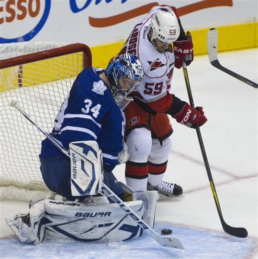 Carolina Hurricane Chad LaRose tries to put the puck past Toronto Maple Leaf goaltender James Reimer during second period NHL hockey action in Toronto on Tuesday Dec. 13, 2011. (AP Photo/The Canadian Press, Pawel Dwulit)