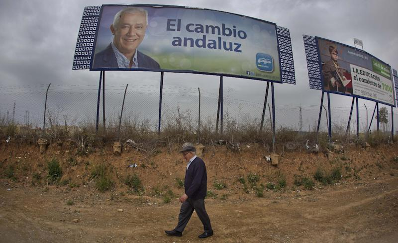 A man walks past a poster with the portrait of the Popular party candidate Javier Arenas, in the outskirts of Seville, Spain, Sunday March 25, 2012. Spaniards are voting in regional elections that could see the conservative Popular party oust Socialist opponents from office in the latter's traditional power base of Andalucia. More than 7 million voters are called to go to the polls Sunday in that southern region and also in northern Asturias. (AP Photo/Miguel Angel Morenatti)