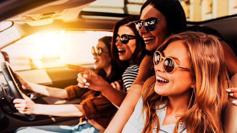 Young driver with cheerful women without seatbelts in car