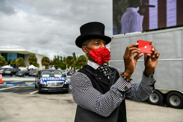 A Biden-Harris supporter takes a photo before the arrival of former US president Barack Obama at a drive-in rally in Miami, Florida on October 24, 2020