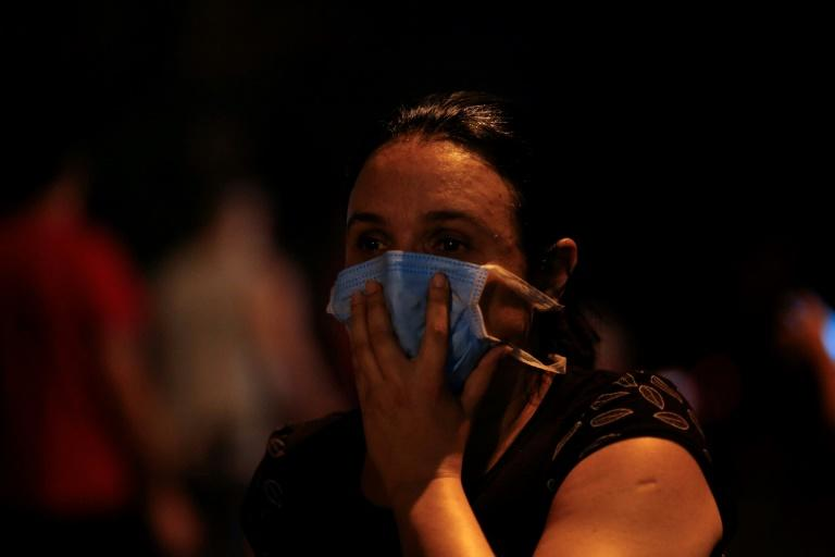 A woman covers her face with a surgical mask to protect herself from the smoke during a fire at the Badim hospital in Rio de Janeiro