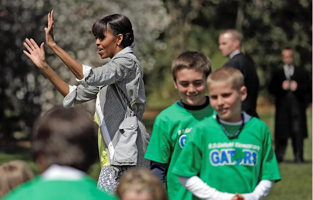 "WASHINGTON, DC - APRIL 04: U.S. first lady Michelle Obama says goodbye to schoolchildren after planting the White House Kitchen Garden on the South Lawn of the White House April 4, 2013 in Washington, DC. For the fifth time, the first lady invited students from ""schools that have made exceptional improvements to school lunches"" from Florida, Massachusetts, Tennessee and Vermont to help her plant the garden. (Photo by Win McNamee/Getty Images)"