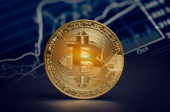 Bitcoin symbol on a golden disc, standing on end in front of a price chart