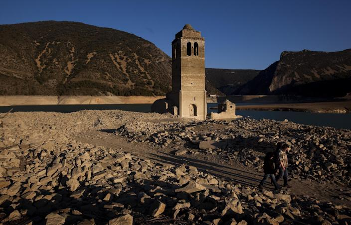 Visitors walk past a church and remains of an ancient village which are usually covered by water are seen inside the reservoir of Mediano, in Huesca, Spain, Tuesday March 13, 2012. One reservoir built in the 1950s, submerging a village called Mediano and its 16th century church, is so low on water that the ruins of buildings which are usually under water are now uncovered. Spain is suffering the driest winter in more than 70 years, adding yet another woe for an economically distressed country that can scarcely afford it. Thousands of jobs and many millions of euros could be in jeopardy. (AP Photo/Emilio Morenatti)