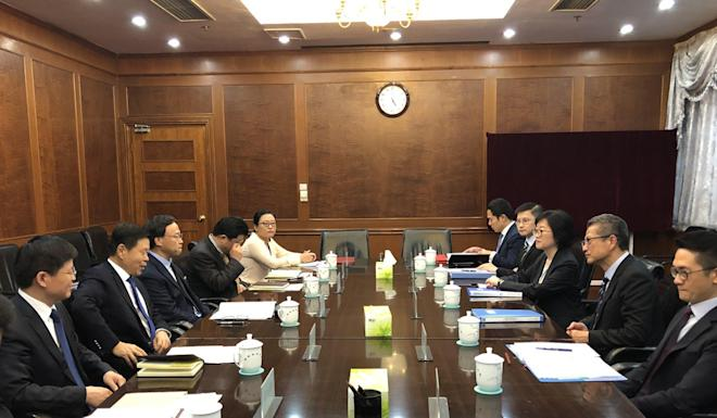Financial Secretary Paul Chan (second right) with Wang Jun (second left), the commissioner of the State Taxation Administration, on July 19 in Beijing. Photo: Handout