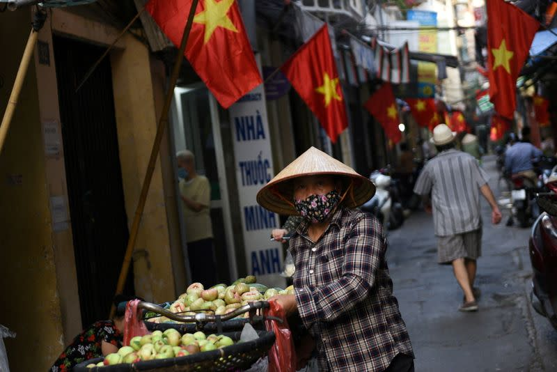 FILE PHOTO: A vendor walks in an alley decorated with national flags ahead of the upcoming elections in Hanoi