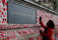 Fran Hall draws one of the last hearts as people paint red hearts to complete the approximately 150,000 hearts being painted onto the National Covid Memorial Wall to commemorate all those who have died of coronavirus, on the Thames Embankment opposite the Houses of Parliament in London, Thursday, April 8, 2021. Bereaved families want the wall of painted hearts to remain a site of national commemoration and are asking the Prime Minister to help make the memorial permanent. (AP Photo/Frank Augstein)