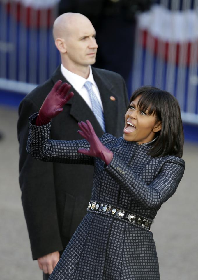 First lady Michelle Obama reacts to the crowd as she walks the inaugural parade route walk down Pennsylvania Avenue en route to the White House, Monday, Jan. 21, 2013, in Washington. Thousands marched during the 57th Presidential Inauguration parade after the ceremonial swearing-in of President Barack Obama. (AP Photo/Gerald Herbert)