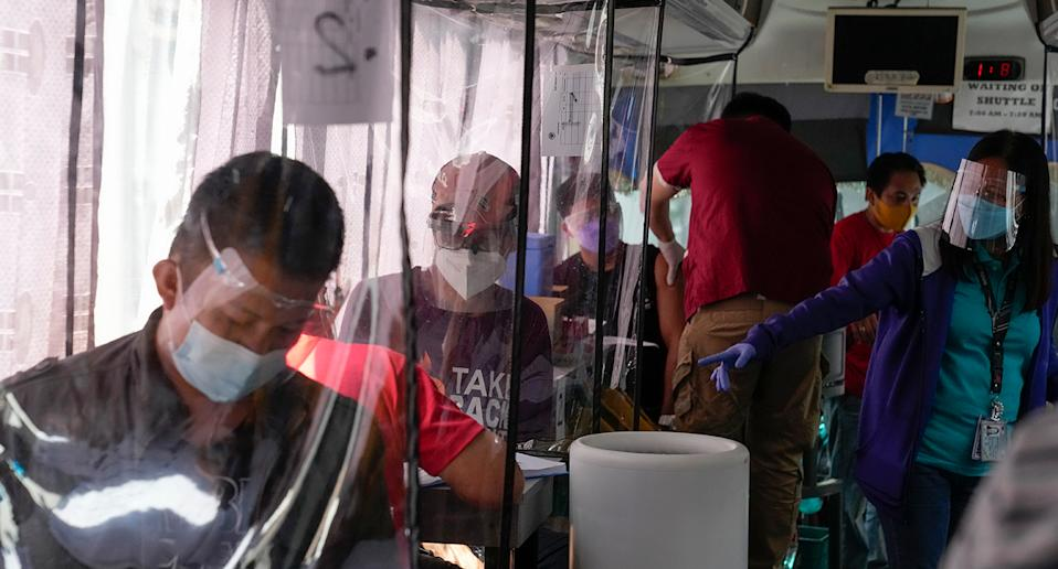 People wait inside a bus used as a mobile Covid-19 vaccination centre to encourage people to get inoculated in Taguig, Philippines on Saturday June 18, 2021. Source: AAP