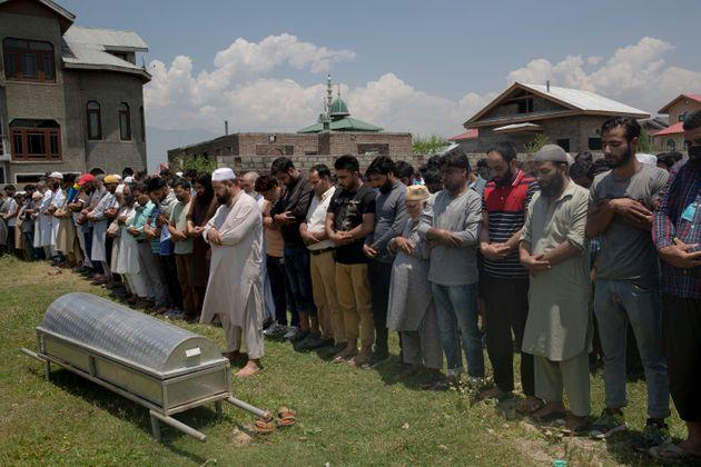 Relatives and neighbors offer prayers near the coffin of civilian Bashir Ahmed Khan, during his funeral on the outskirts of Srinagar on July 1, 2020.