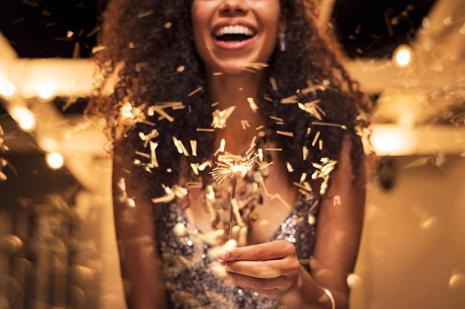 Cheerful young woman holding single sparkler in hand outdoor. Detail of african girl celebrating new year'u2019s eve with bengal light. Closeup of beautiful woman holding a sparkling stick at party night.