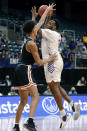 Abilene Christian forward Airion Simmons, right, puts up a shot over Lamar center David Muoka, left, during the first half of an NCAA college basketball game in the Southland Conference semifinals Friday, March 12, 2021, in Katy, Texas. (AP Photo/Michael Wyke)