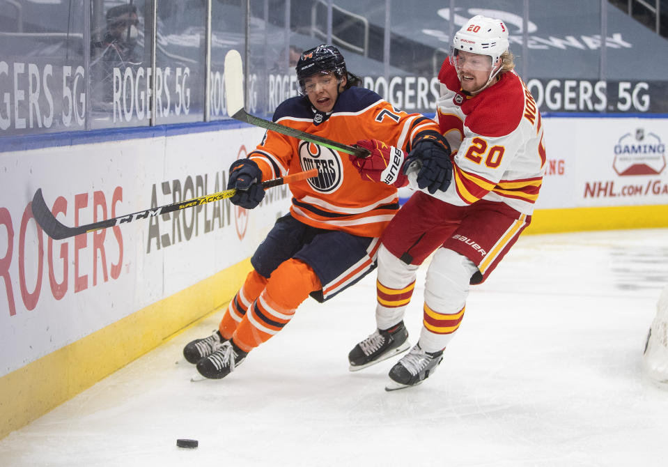 Edmonton Oilers' Ethan Bear (74) and Calgary Flames' Joakim Nordstrom (20) compete for the puck during the third period of an NHL hockey game Friday, April 2, 2021, in Edmonton, Alberta. (Jason Franson/The Canadian Press via AP)