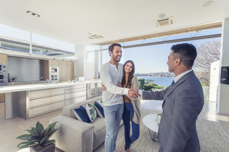 Real estate agent with couple in luxury home, shaking hands.