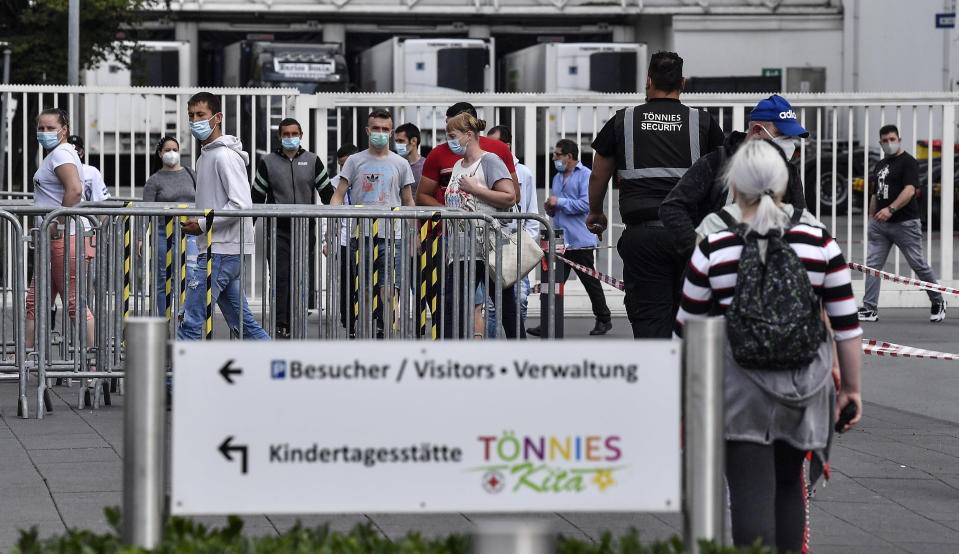 Workers with face masks enter the Toennies meatpacking plant, Europe's biggest slaughterhouse, where the German Bundeswehr army helps to build up a test center for coronavirus in Rheda-Wiedenbrueck, Germany, Friday, June 19, 2020. Hundreds of new COVID-19 cases are linked to a large meatpacking plant, officials ordered the closure of the slaughterhouse, as well as isolation and tests for everyone else who had worked at the Toennies site — putting about 7,000 people under quarantine. (AP Photo/Martin Meissner)