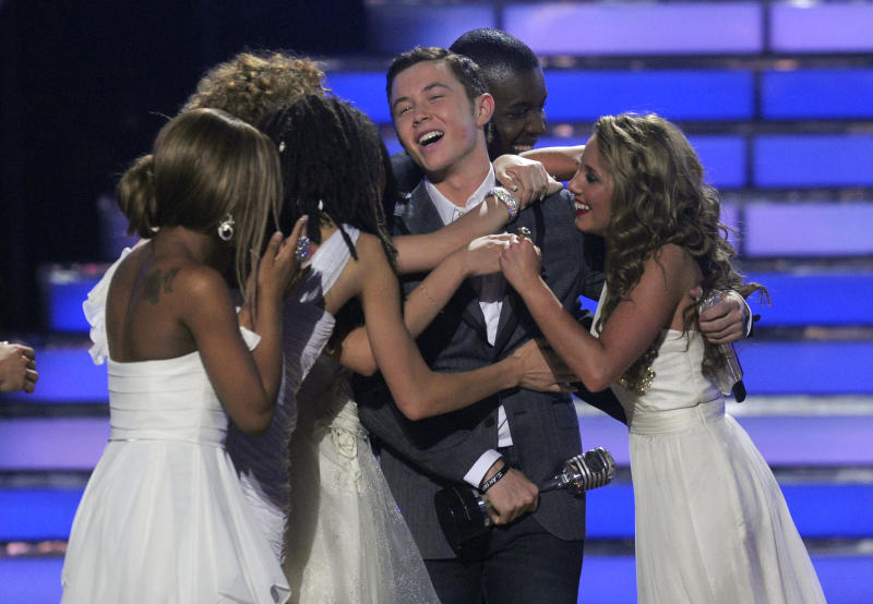 """Scotty McCreery reacts after winning at the """"American Idol"""" finale on Wednesday, May 25, 2011, in Los Angeles. Other """"American Idol"""" contestants are seen congratulating him. (AP Photo/Chris Pizzello)"""