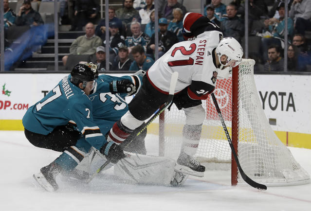 Arizona Coyotes' Derek Stepan (21) scores a goal past San Jose Sharks' Dylan Gambrell (7) and goalie Aaron Dell, second from left, in the second period of an NHL hockey game, Tuesday, Dec. 17, 2019, in San Jose, Calif. (AP Photo/Ben Margot)