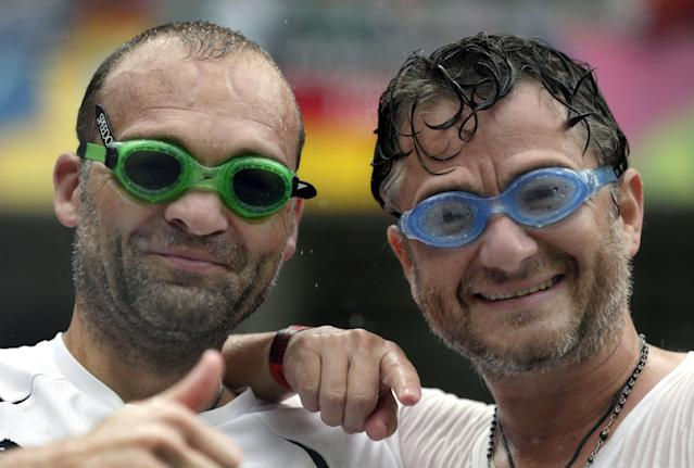 Soccer fans wear swimming goggles as rain pours down prior to the group G World Cup soccer match between the USA and Germany at the Arena Pernambuco in Recife, Brazil, Thursday, June 26, 2014. (AP Photo/Petr David Josek)