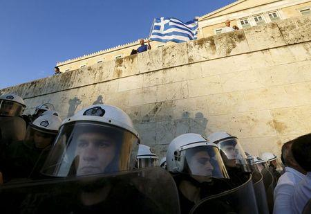 A protester waves a Greek flag as riot policemen stand guard at the parliament building during a rally calling on the government to clinch a deal with its international creditors and secure Greece's future in the Eurozone, in Athens, Greece, June 22, 2015. REUTERS/Yannis Behrakis