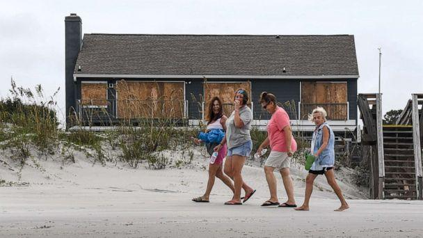 PHOTO: Women walk in front of a boarded up house on the beach in North Litchfield, S.C., Sept. 4, 2019. (Independent Mail/USA Today Network)