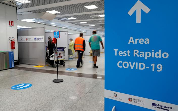 People walk next to a testing site at Fiumicino Airport in Rome, Italy - Remo Casilli/Reuters