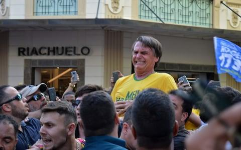 Jair Bolsonaro gestures after being stabbed in the stomach during a campaign rally in Juiz de Fora - Credit: RAYSA LEITE/AFP