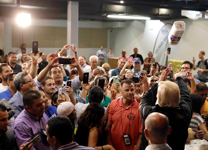 President Trump throws a roll of paper towels to a crowd affected by Hurricane Maria as he visits a disaster relief distribution center in San Juan, Puerto Rico, Oct. 3, 2017. (AP Photo/Evan Vucci)