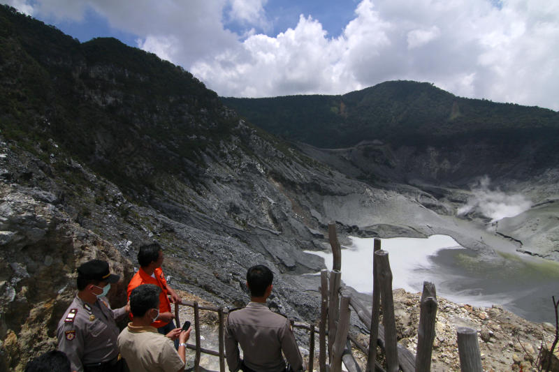 Indonesian officials examine the crater of Tangkuban Perahu volcano in Subang, West Java, Indonesia, Thursday, March 7, 2013. Indonesian authorities are closely monitoring the smoking volcano popular with tourists on Java island and are urging everyone to stay off the mountain's slope after it spewed smoke and ash nearly 500 meters (1,640 feet) into the air since Monday. Scientists have put it on the second-highest alert level. (AP Photo/Kusumadireza)