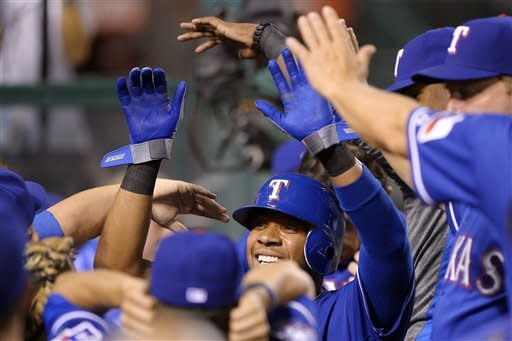 Texas Rangers' Elvis Andrus is congratulated by teammates after scoring on a double by Michael Young during the third inning of their baseball game against the Los Angeles Angels, Wednesday, Sept. 19, 2012, in Anaheim, Calif. (AP Photo/Mark J. Terrill)
