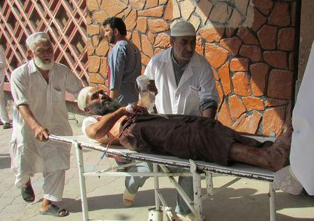 Afghan men carry an injured man to a hospital after a suicide attack in Nangarhar province
