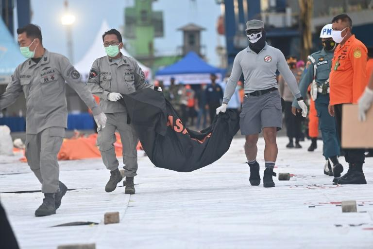Forensic policemen carry a bag containing debris from the crash