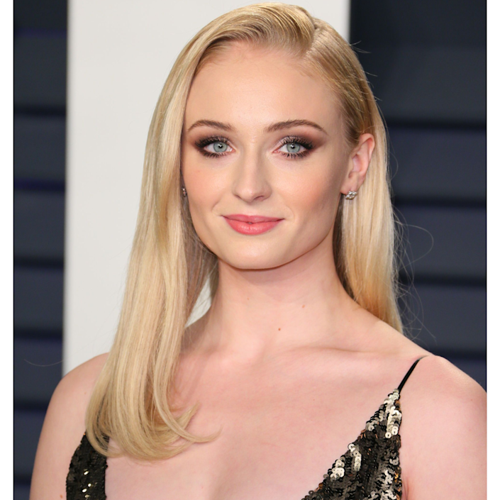 """You're probably most accustomed to seeing Sophie Turner with <a href=""""https://www.allure.com/gallery/most-flattering-red-hair-colors-for-every-skin-tone?mbid=synd_yahoo_rss"""" rel=""""nofollow noopener"""" target=""""_blank"""" data-ylk=""""slk:vibrant red strands"""" class=""""link rapid-noclick-resp"""">vibrant red strands</a>, but this true pale blonde is uniquely flattering against the rosy undertones in her skin. It's a shade that works best if your base is relatively light on its own — otherwise, the hue can look a bit forced. """"Pale blonde hair colors pair well with warm tones,"""" says Ikeda. """"In Sophie's case, her shade of blonde enhances the warmer underlying tones in her skin."""" Plus, Turner's makeup, especially her pink blush, keeps her from looking washed out."""