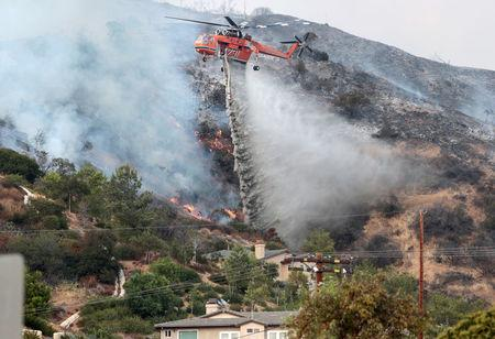 Water is dropped above homes in Sun Valley during the La Tuna Canyon fire over Burbank. REUTERS/ Kyle Grillot