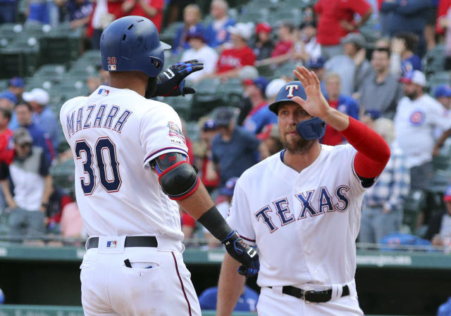 Texas Rangers right fielder Nomar Mazara (30) is greeted at the plate by Hunter Pence after a two-run home run in the ninth inning of a baseball game against the Chicago Cubs Thursday, March 28, 2019 in Arlington, Texas. (AP Photo/Richard W. Rodriguez)