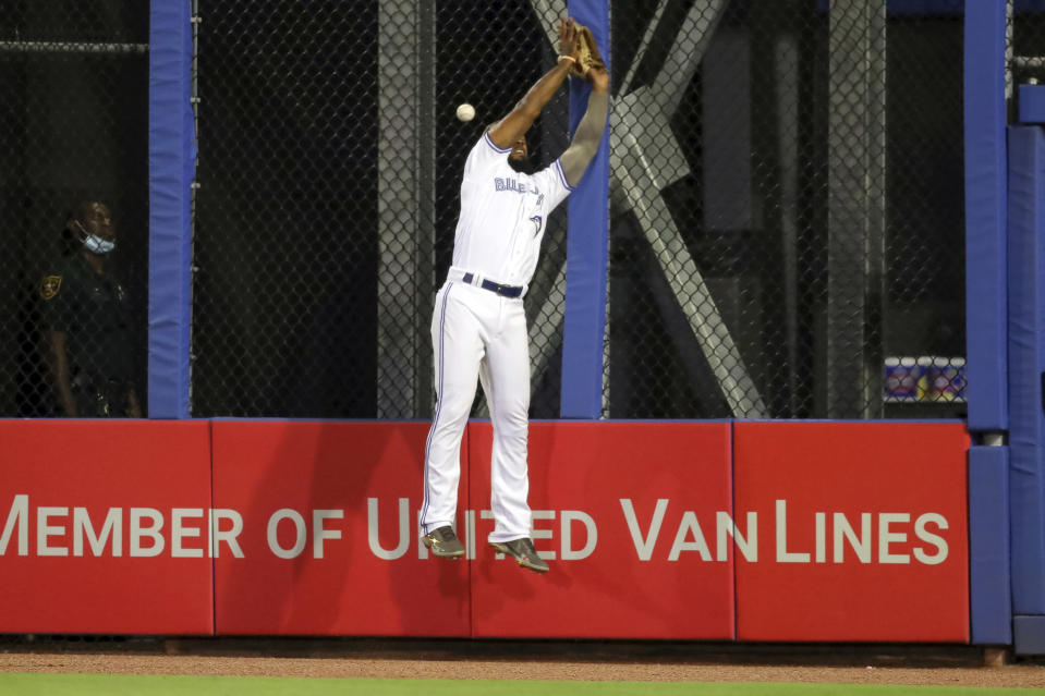 Toronto Blue Jays right fielder Teoscar Hernandez cannot catch a fly ball by Philadelphia Phillies' Alec Bohm ,allowing a run to score, during the seventh inning of a baseball game Friday, May 14, 2021, in Dunedin, Fla. (AP Photo/Mike Carlson)