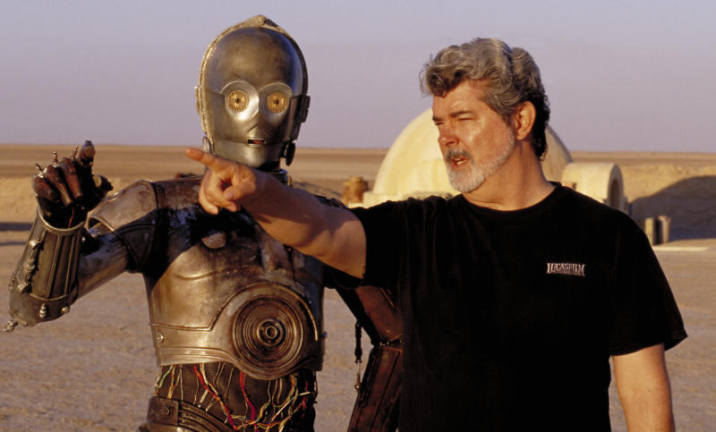 """** FILE ** In this undated publicity photo released by Lucasfilm Ltd. & TM, director George Lucas directs actor Anthony Daniels, who plays the robot C-3PO, in """"Star Wars II: Attack of the Clones,"""" on location in the Tunisian desert. Dozens of groundbreaking technologies were developed for the production of the Star Wars movies. There's no mistaking the similarities. A childhood on a dusty farm, a love of fast vehicles, a rebel who battles an overpowering empire, George Lucas is the hero he created, Luke Skywalker. (AP Photo/Lucasfilm Ltd. & TM, LisaTomasetti)"""