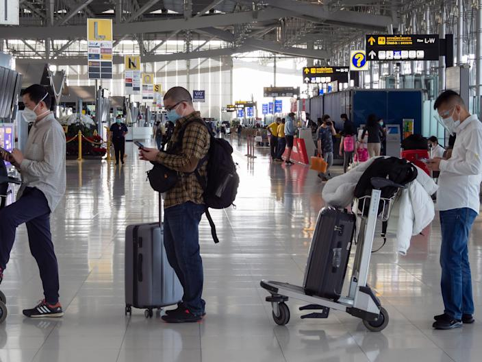 Bangkok, Thailand - April 11, 2021 : asian passengers using smartphones to checking news and waiting in row to check-in for airplane flights in covid-19 or coronavirus pandemic at airport terminal.