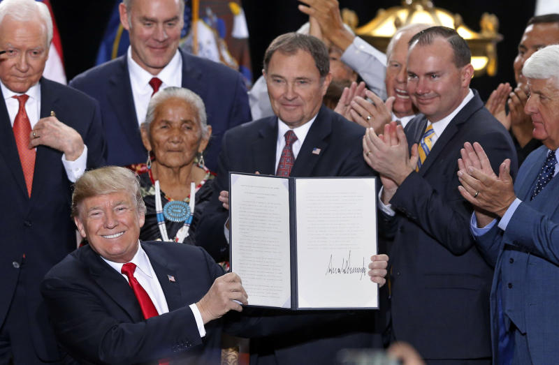 FILE - In this Monday, Dec. 4, 2017, file photo, President Donald Trump holds up a signed proclamation to shrink the size of Bears Ears and Grand Staircase Escalante national monuments, at the Utah State Capitol, in Salt Lake City. The U.S. government is unveiling its final management plan for the Bears Ears National Monument on tribal lands home to ancient cliff dwellings and other artifacts in Utah that was significantly downsized by President Trump. Conservation groups, tribes and an outdoor retail company have sued challenging the downsizing. (AP Photo/Rick Bowmer, File)