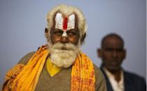 """An Indian Hindu Sadhu (left) and a newly initiated Sadhu look on near their tent at the Kumbh Mela in Allahabad on February 19, 2013. Authorities at the festival on Sunday said the last batch of holy men marked the end of the Kumbh by plunging into the river Ganges and other pilgrims filled the """"Ganga Jal"""" (holy water) in plastic bottles for religious ceremonies at home"""