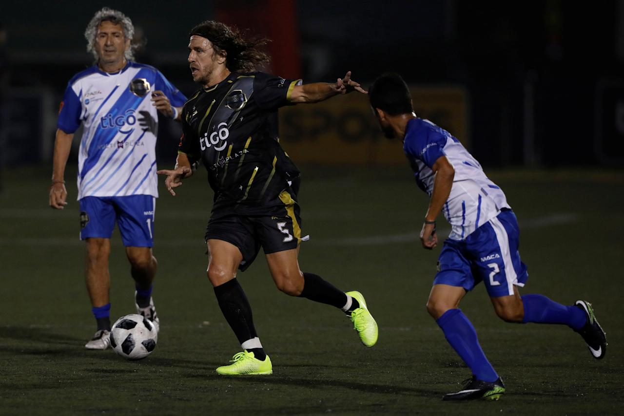 "Former Spanish soccer player Carles Puyol (C) plays ball with former Salvadorean soccer players Jorge ""Magico"" Gonzalez (L) and Roberto Garcia (R) during an exhibition match at Las Delicias Stadium in Santa Tecla, El Salvador May 20, 2018. REUTERS /Jose Cabezas"