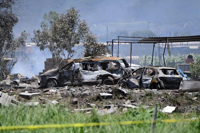 <p>Charred vehicles are seen at the site of a series of explosions at fireworks warehouses in Tultepec, central Mexico, on July 5, 2018. – At least 19 people were killed, including rescue workers who died saving others' lives, officials said. The initial explosion occurred around 9:30 am (1430 GMT), then spread to other warehouses just as police and firefighters began attending to the first victims. (Photo: Pedro Pardo/AFP/Getty Images) </p>