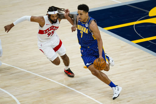 Indiana Pacers guard Malcolm Brogdon (7) drives on Toronto Raptors forward DeAndre' Bembry (95) during the first half of an NBA basketball game in Indianapolis, Sunday, Jan. 24, 2021. (AP Photo/Michael Conroy)